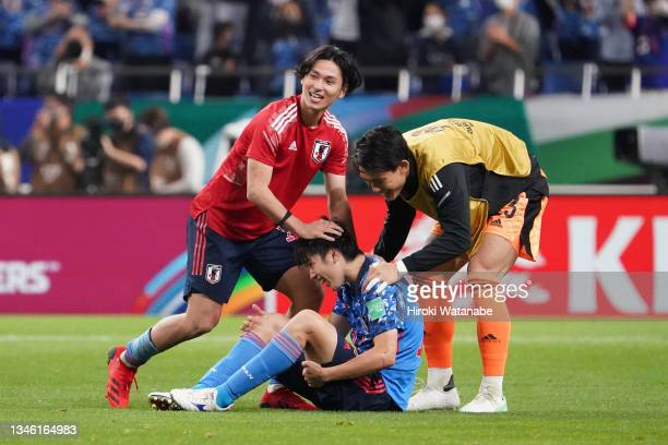 Ao Tanaka of Japan is congratulated by his team mates Takumi Minamino and Kosei Tani after his side's 2-1 victory in the FIFA World Cup Asian...
