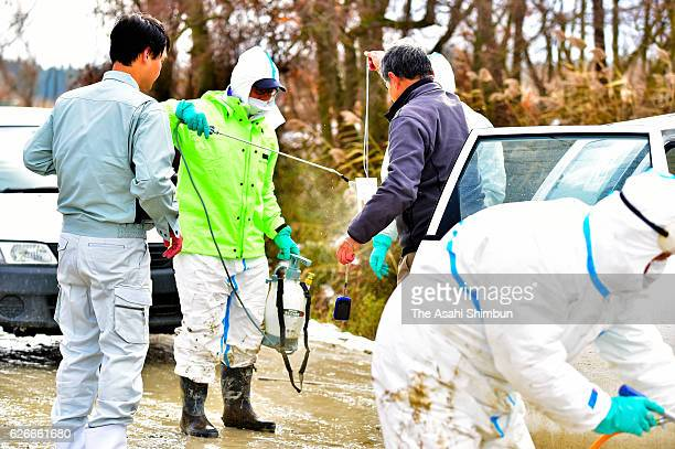 Aomori prefectural government workers sanitize in front of a duck farm where birds were found to be infected with the avian flu virus on November 29...
