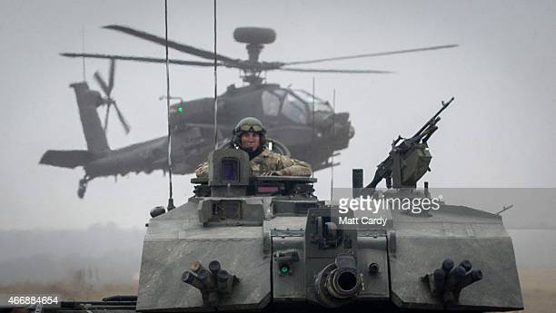 Apache helicopters hover above a column of Army vehicles including Challenger 2, Warrior and FV 432's belonging to 1 Yorks and Kings Royal Hussars as...