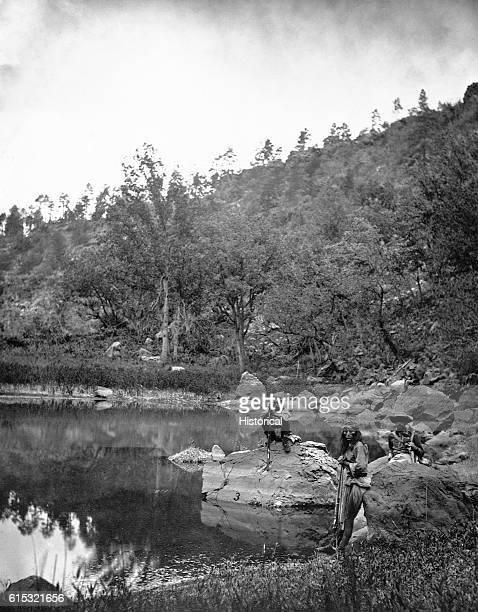 Apache scouts attached to the 1873 Wheeler Survey gathering near a lake White Mountains Arizona ca 1873