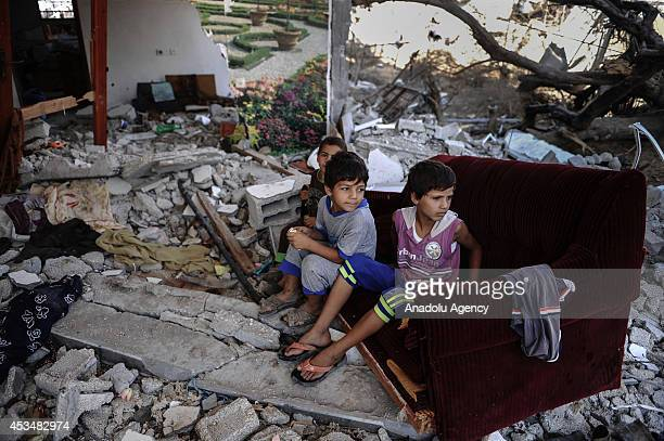 APalestinian kids sit on a couch amongst the wreckages of a building as Palestinians try to collect usable belongings amongst the ruins during the...