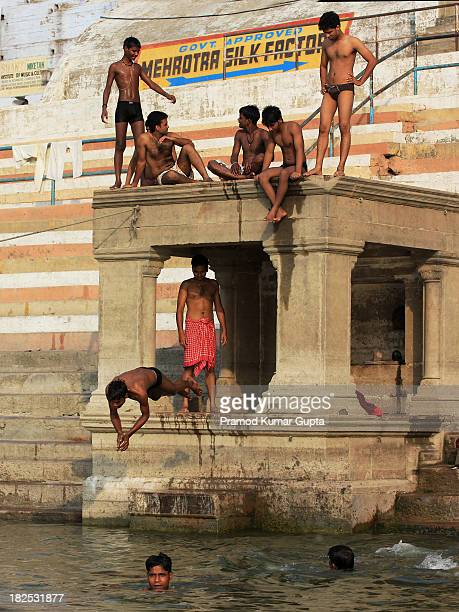 Apart from religious reasons, people come to river Ganges for fun also. Here, a man is diving while others are enjoying the morning sun. Picture was...