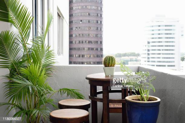 apartment balcony table with plants - balcony stock pictures, royalty-free photos & images