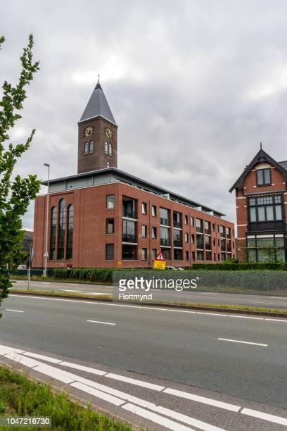 apartment building with bell tower halfweg - boek stock-fotos und bilder