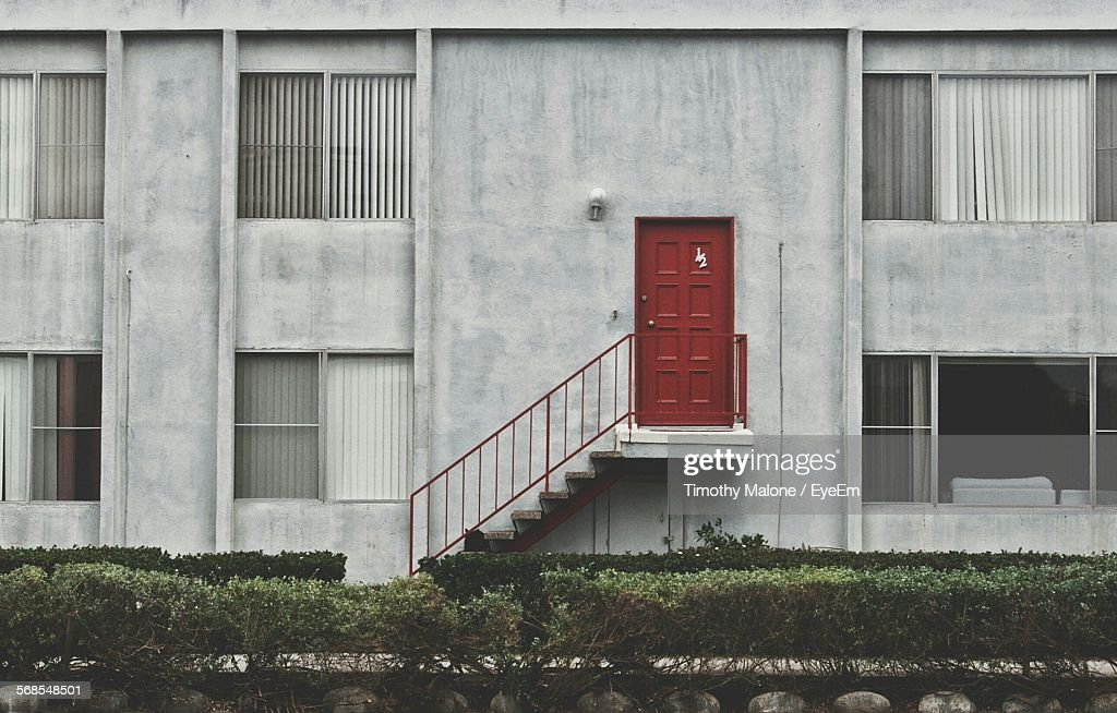 Apartment Building With Closed Red Door On Wall : Stock Photo
