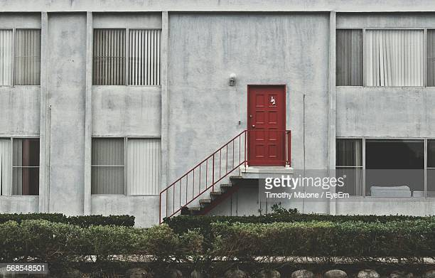 Apartment Building With Closed Red Door On Wall