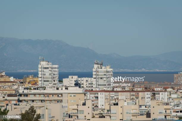 apartment buildings and hotels in bright sunlight with the bay of málaga and mountains in the background - dorte fjalland fotografías e imágenes de stock