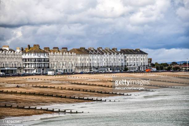 apartment buildings near the beach and waterfront of eastbourne, uk - eastbourne stock pictures, royalty-free photos & images