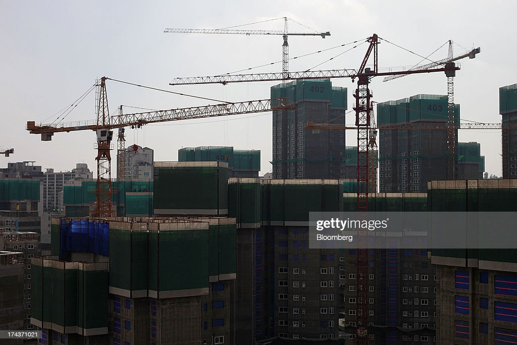 Apartment buildings stand under construction in the district of Mapo in Seoul, South Korea, on Wednesday, July 24, 2013. South Koreas economy grew the most in more than two years, on stronger government spending and private consumption even as a slowdown in China clouds the outlook. Photographer: Woohae Cho/Bloomberg via Getty Images