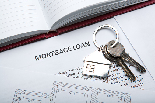 apartment keys with house key chain and a mortgage loan document and a diary 866244810