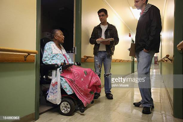 Apartment resident Mozelle Tarver speaks with Democratic party volunteers Chris Lettero and Matt Lattanzi on October 28 2012 in Youngstown Ohio The...