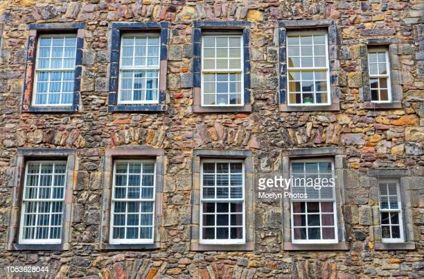 apartment windows - stone house stock pictures, royalty-free photos & images