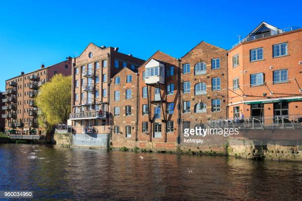 apartments, bars and restaurants on the river aire in leeds, yorkshire. - leeds skyline stock photos and pictures