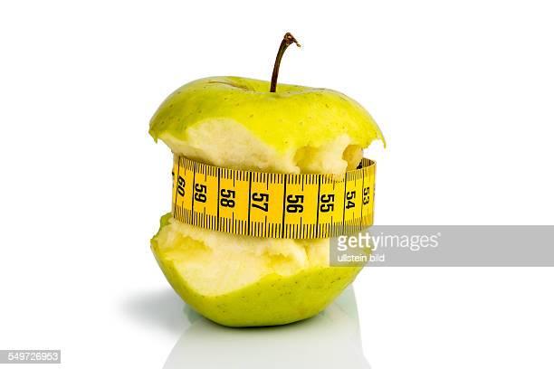 Apfel mit einem Maßband Symbolfoto für Diät und gesunde vitaminreiche Ernährung