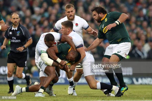 Aphiwe Dyantyi of South Africa is held in the tackle by England's Owen Farrell and Kyle Sinckler during the second test match between South Africa...
