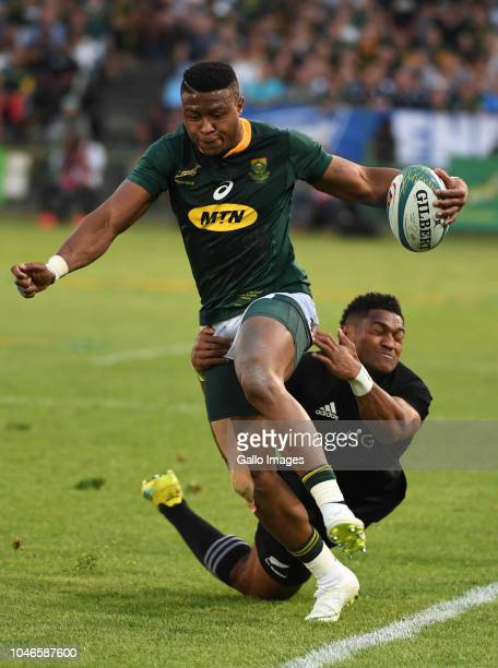 Aphiwe Dyantyi of the Springboks tackled by Waisake Naholo of New Zealand during the Rugby Championship match between South Africa and New Zealand at...