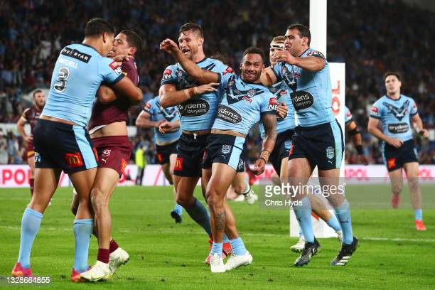 Api Koroisau of the Blues celebrates with team mates after scoring a try as Latrell Mitchell of the Blues wrestles with Dane Gagai of the Maroons...