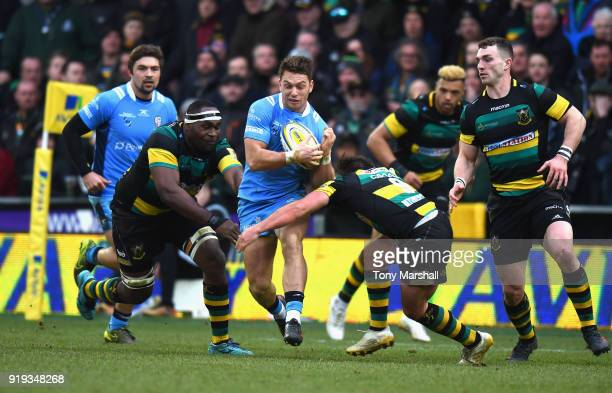 Api Ratuniyarawa and Nic Groom of Northampton Saints tackle Alex Lewington of London Irish during the Aviva Premiership match between Northampton...