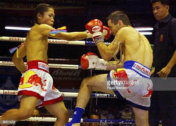Apinya Sor Pumarin a transvestite Muay Thai kickboxer fights American boxer Anthony DeMaio from New York at the Lumpini stadium February 21 2004 in...