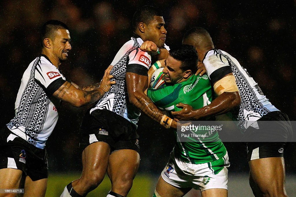 Apirana Pewhairangi of Ireland (2nd R) is tackled by Fiji's Kevin Naiqama (2nd L) and Waisale Ligani Naiqama (R) during the Rugby League World Cup Group A match between Fiji and Ireland at Spotland Stadium on October 28, 2013 in Rochdale, England.