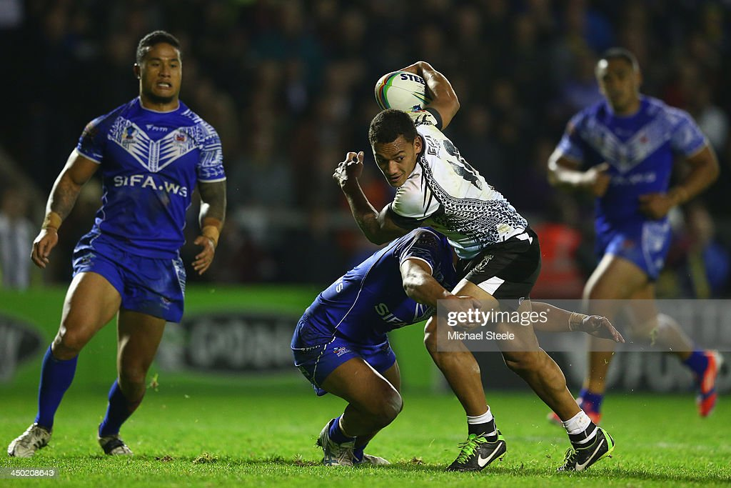Apisai Koroisau of Fiji looks to offload as Anthony Milford of Samoa holds on in the tackle during the Rugby League World Cup Quarter Final match between Samoa and Fiji at The Halliwell Jones Stadium on November 17, 2013 in Warrington, England.