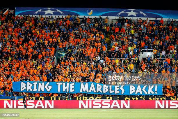 Apoel FC's fans hold a banner reading in English 'bring the marbles back' during the UEFA Champions League football match between Apoel FC and...