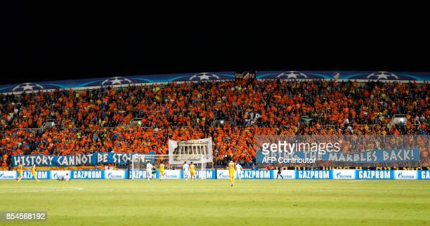 Apoel FC's fans hold banners reading in English 'history cannot be stolen bring the marbles back' during the UEFA Champions League football match...