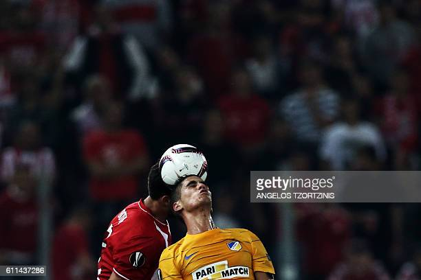 Apoel Nicosia' Cypriot forward Pieros Sotiriou and Olympiacos' spanish defender Alberto Botia go for q heqder during the UEFA Europa League group...