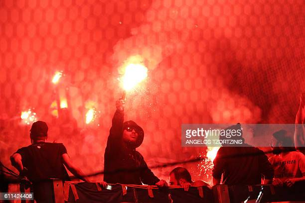 Apoel's fans hold flares before the start of the UEFA Europa League group football match between Olympiakos FC and Apoel Nicosia on September 29,...