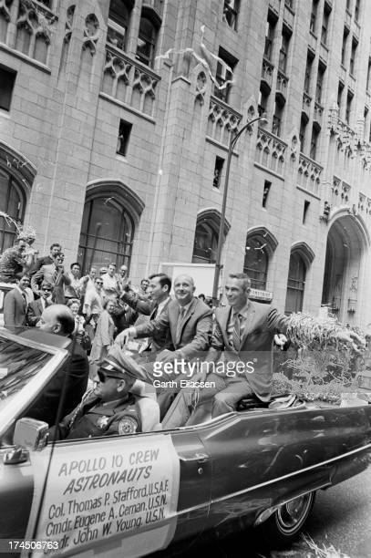 Apollo 10 astronauts Gene Cernan Tom Stafford and John Young with San Francisco Mayor Joseph Alioto wave from a convertible limousine during a ticker...