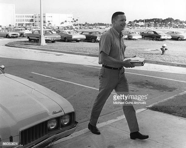 Apollo 11 astronaut Neal Armstrong carries his training manuals as he arrives at the flight crew training building of the NASA Kennedy Space Center...