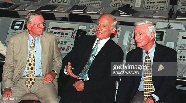Apollo 11 Commander Neil Armstrong and Apollo 17 Commander Gene Cernan listen as Apollo 11 crewmember Edwin Aldrin answers questions from the media...