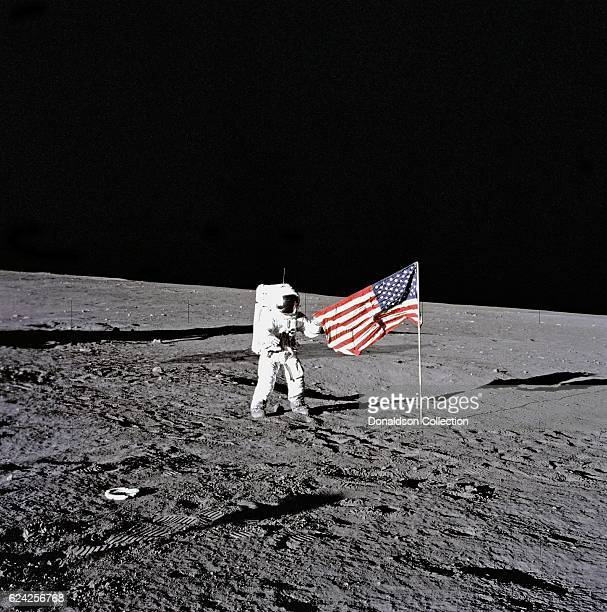 Apollo 12 commander Charles 'Pete' Conrad Jr holds the American flag during his first space walk becoming the third man to walk on the Moon on...