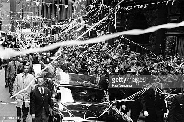 Apollo 13 astronauts James Lovell on the right wave to the crowd while riding in an open convertible during a ticker tape parade celebrating their...
