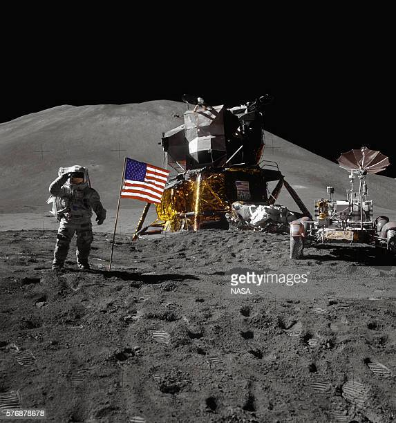 Apollo 15 astronaut Jim Irwin stands on the moon saluting beside an American flag