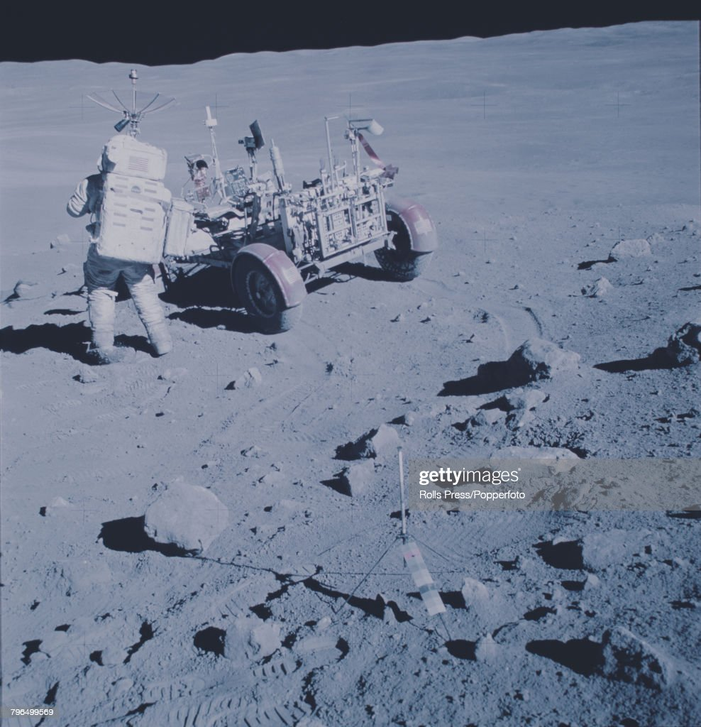 Apollo 16 Commander John Young (1930-2018), wearing his space suit, attends to the Lunar Rover vehicle on the lunar surface of the Moon during a moon walk in the lunar highlands by the Apollo 16 astronauts during their space mission in April 1972.
