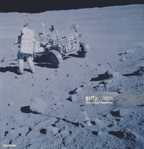 Apollo 16 Commander John Young wearing his space suit attends to the Lunar Rover vehicle on the lunar surface of the Moon during a moon walk in the...