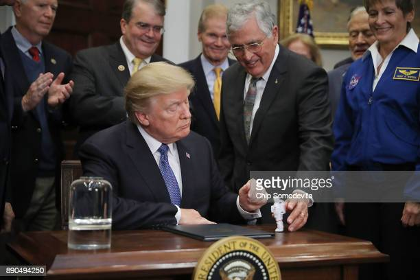 Apollo 17 astronaut and former US Senator Jack Schmitt gives a plastic astronaut figurine to US President Donald Trump after he signed 'Space Policy...