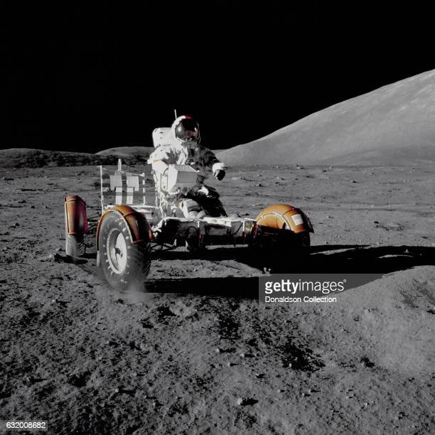 Apollo 17 commander Eugene A Cernan rides the Lunar Roving Vehicle during his first space walk at the TaurusLittrow landing site becoming the last...