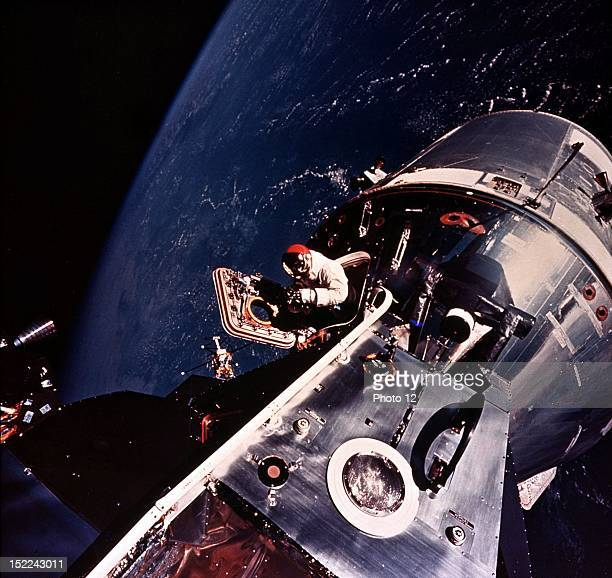 Apollo 9 astronaut david Scott is photographed during E V A by Astronaut Russell Schweickart from the porch of LEM Scott stands in the open hatch of...
