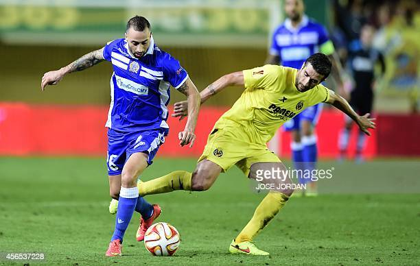 Apollon Limassol's midfielder from Greece Photis Papoulis vies with Villarreal's midfielder Cani during the Europa League football match Villarreal...
