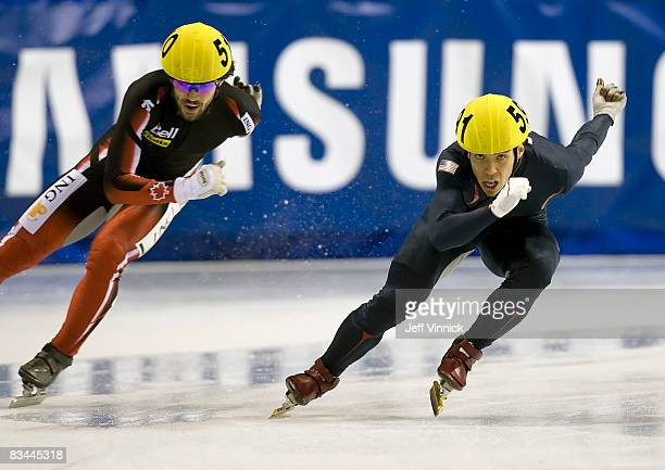 Apolo Anton Ohno edges out Charles Hamelin of Canada at the finish line for first place during the men's 5000m relay at the ISU World Cup Speed short...