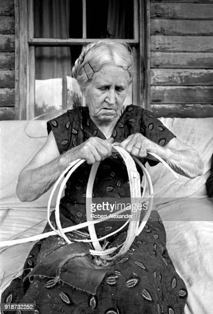 Appalachian basketmaker Mary Helton ties together the ribs of a split oak basket as she sits on her porch in Abingdon Virginia