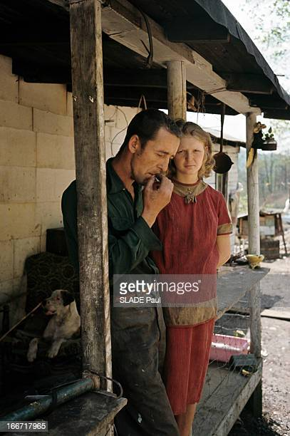 Appalachian Valley Dans le nordest américain dans les Appalaches sous l'appentis d'une baraque un homme de profil portant des vêtements tâchés appuyé...