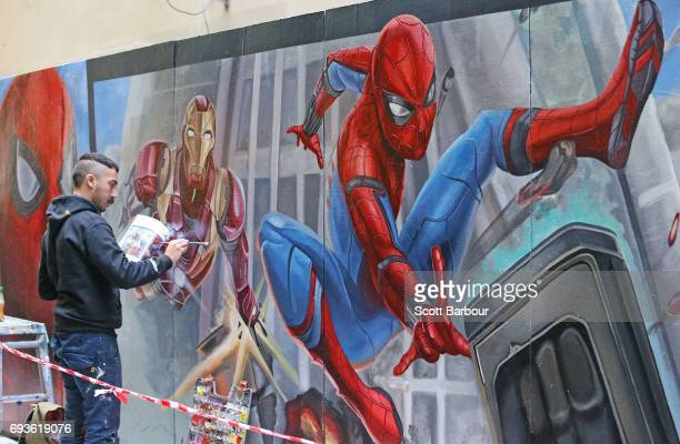 Apparition Media artist David Lee Pereira paints the final parts of the SpiderMan Homecoming mural on June 8 2017 in Melbourne Australia Apparition...