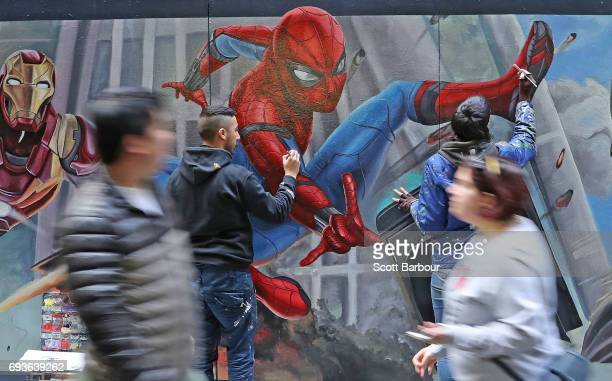 Apparition Media artists David Lee Pereira and Tayla Broekman paint the final parts of the SpiderMan Homecoming mural on June 8 2017 in Melbourne...