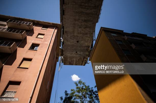 TOPSHOT Appartment buildings are seen under the Morandi motorway bridge two days after a section collapsed in Genoa on August 16 2018 A vast span of...