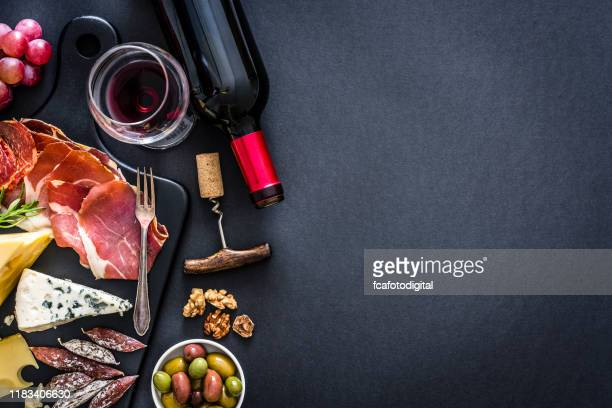 appetizer frame: red wine, iberico ham and cheese on rustic table - french culture stock pictures, royalty-free photos & images