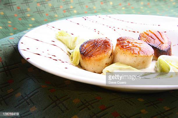 Appetizer of fresh scallops with leeks on plate