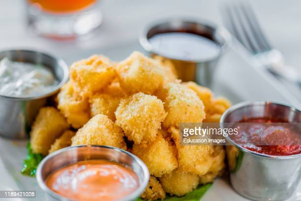 Appetizer of fried cheese curds and dipping sauces.